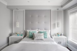 Horizontal image of modern girls bedroom, with large headboard and matching side tables and lamps. Brightly lit with pastel colours and pops of turquoise.